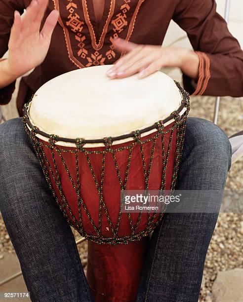 Woman beating drum