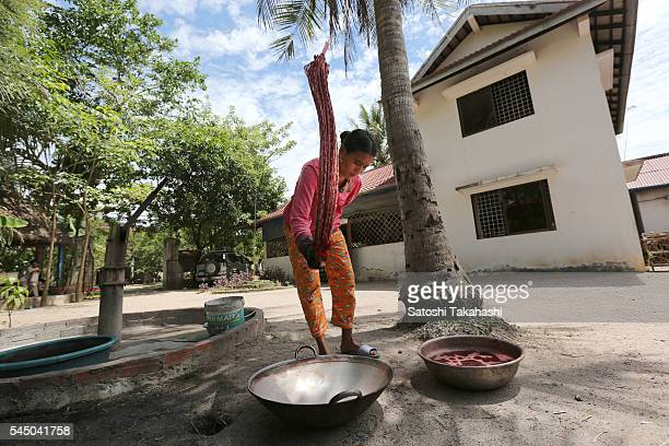 CYK'S WEAVING TRAINING CENTER TAKEO PROVINCE CAMBODIA A woman beats a dyed silk into a tub for dyes can be uniformly spread to the silk