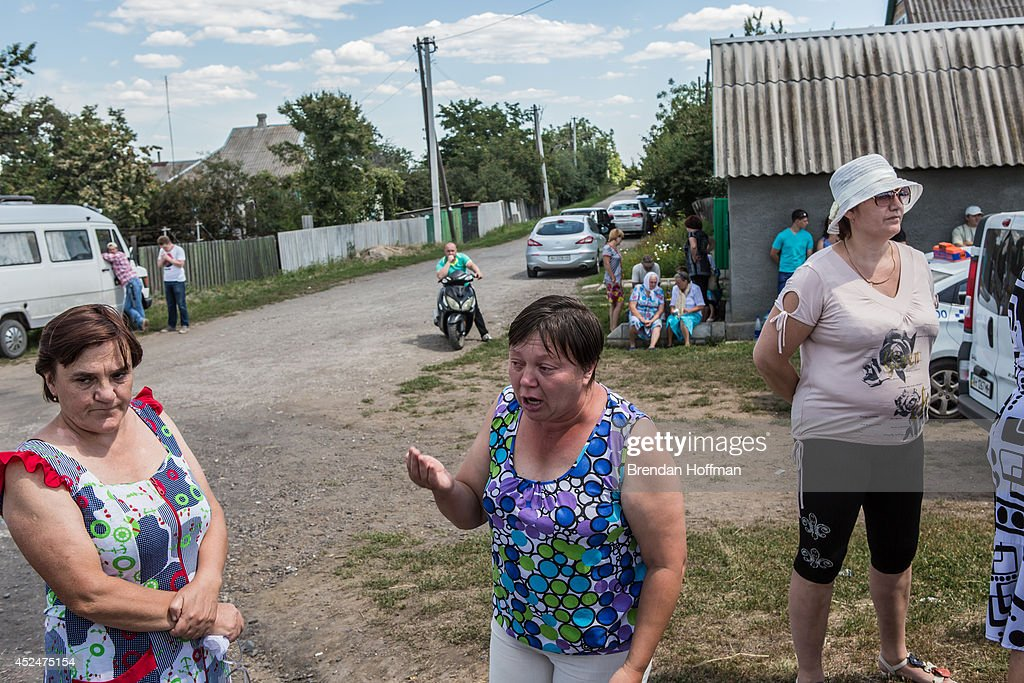 A woman becomes emotional as she talks with reporters while local residents gather to watch as the bodies of victims of Malaysia Airlines flight MH17 are removed from the scene of the crash on July 21, 2014 in Grabovo, Ukraine. Malaysia Airlines flight MH17 was travelling from Amsterdam to Kuala Lumpur when it crashed killing all 298 on board including 80 children. The aircraft was allegedly shot down by a missile and investigations continue over the perpetrators of the attack.
