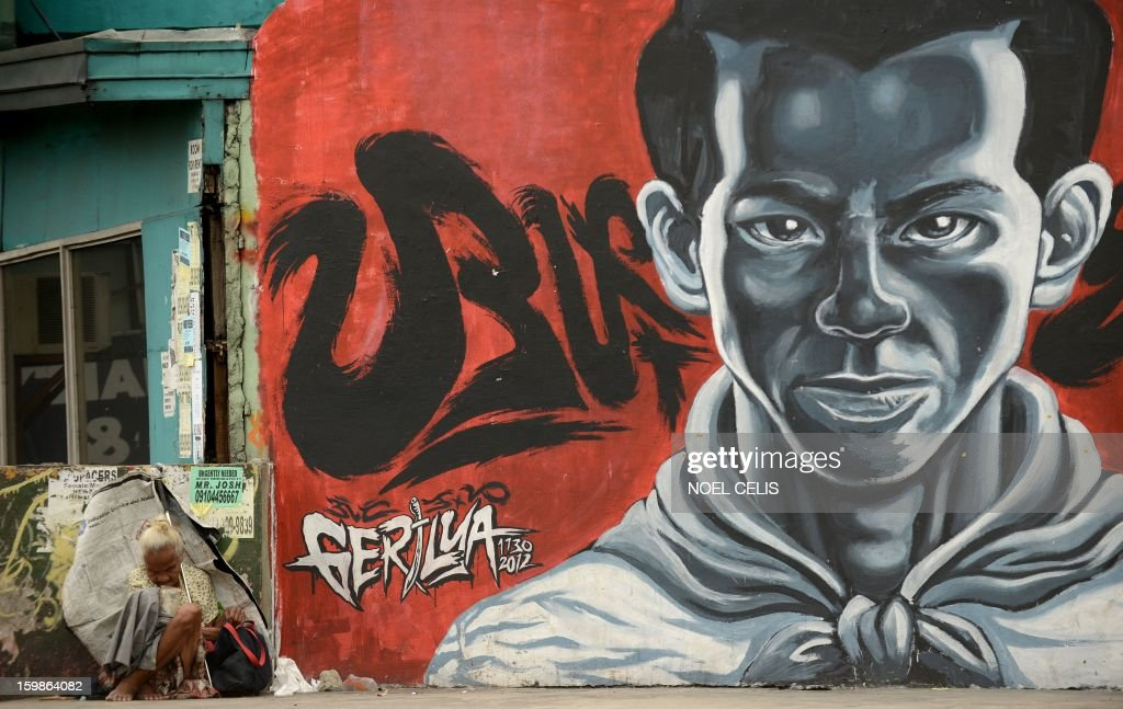 A woman beg for alms from passers-by near a wall painted with street art featuring Philippine working class hero Andres Bonifacio at an overpass in Manila on January 22, 2013. Andres Bonifacio led Katipuneros in 1896 to a failed war of independence against Spain's colonial rulers.