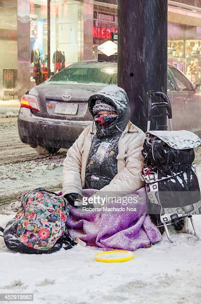 Woman begger under the snowfall in Toronto during an important snow fall during winter