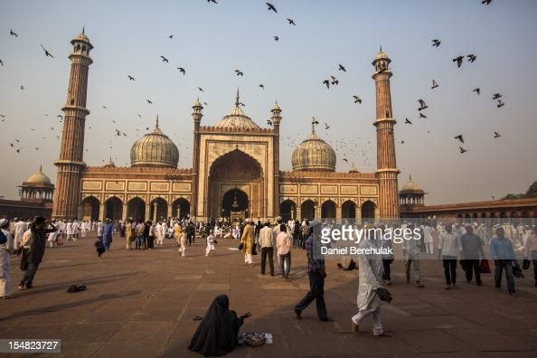A woman begs for alms as Indian Muslims mingle after Eid alAdha prayers at Jama Masjid on October 27 2012 in New Delhi India Eid alAdha also known as...