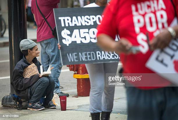 A woman begs for change as fast food workers and community activists protest outside a McDonald's restaurant in the Loop on June 22 2015 in Chicago...