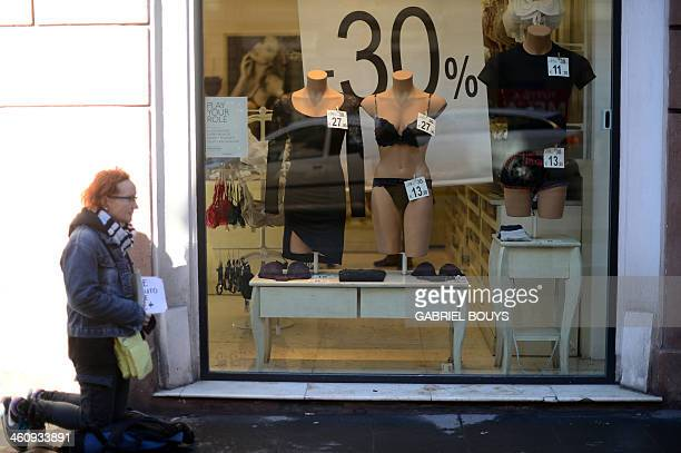 A woman begs for money next to a shop window during winter sales on January 6 2014 in Rome AFP PHOTO / GABRIEL BOUYS
