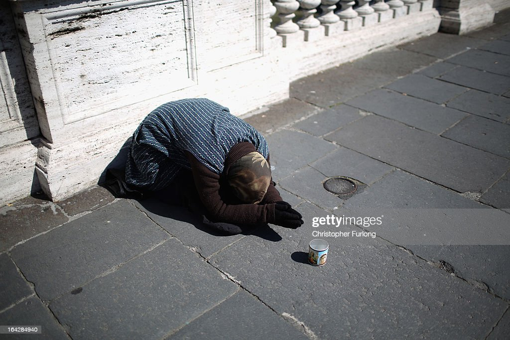 A woman begs on a bridge on March 22, 2013 in Rome, Italy. Newly elected Pope Francis and the Vatican are preparing for the new pontiff's first Easter week which will incorporate the pope washing the feet of prisoners in a youth detention centre in Rome next Thursday.