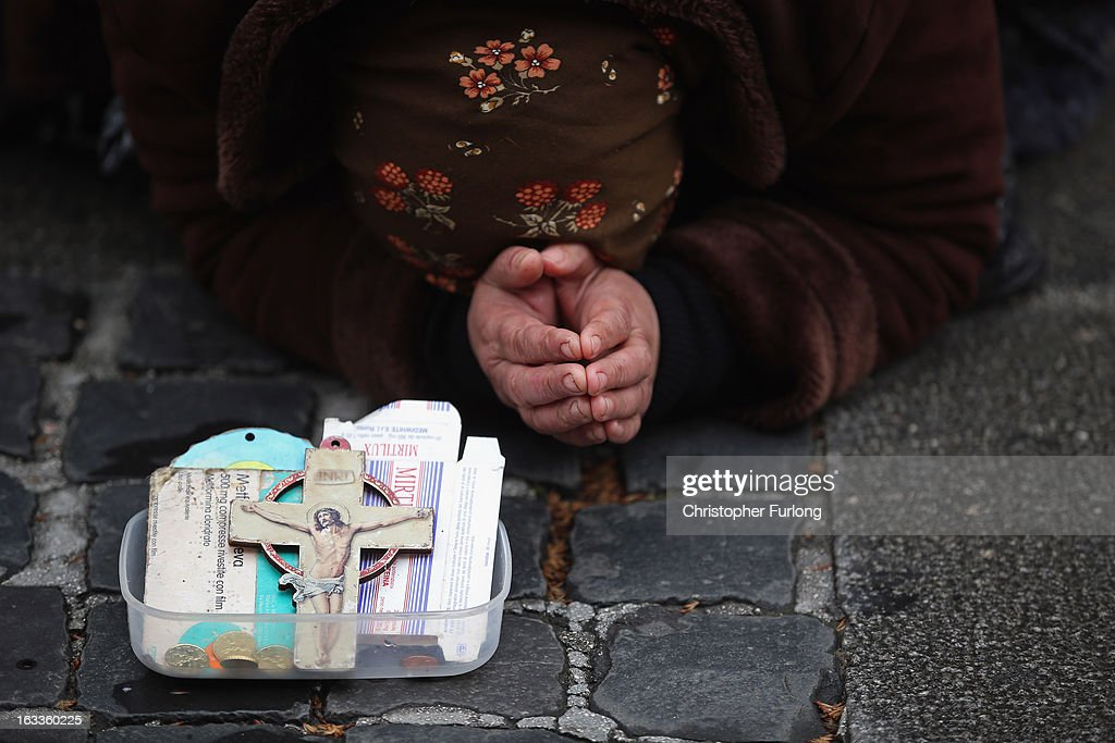 A woman begs outide the city walls of the Vatican on March 8, 2013 in Rome, Italy. Cardinals are set to enter the conclave to elect a successor to Pope Benedict XVI after he became the first pope in 600 years to resign from the role. The conclave is scheduled to start on March 12 inside the Sistine Chapel and will be attended by 115 cardinals as they vote to select the 266th Pope of the Catholic Church.