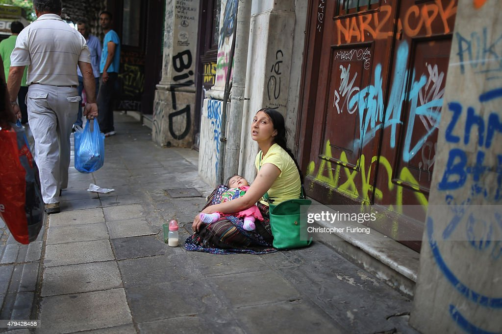 A woman begs the street on the eve of Greece's austerity vote on July 4 2015 in Athens Greece The people of Greece are preparing to vote in the...