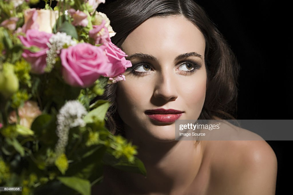 Woman behind a bunch of flowers : Stock Photo