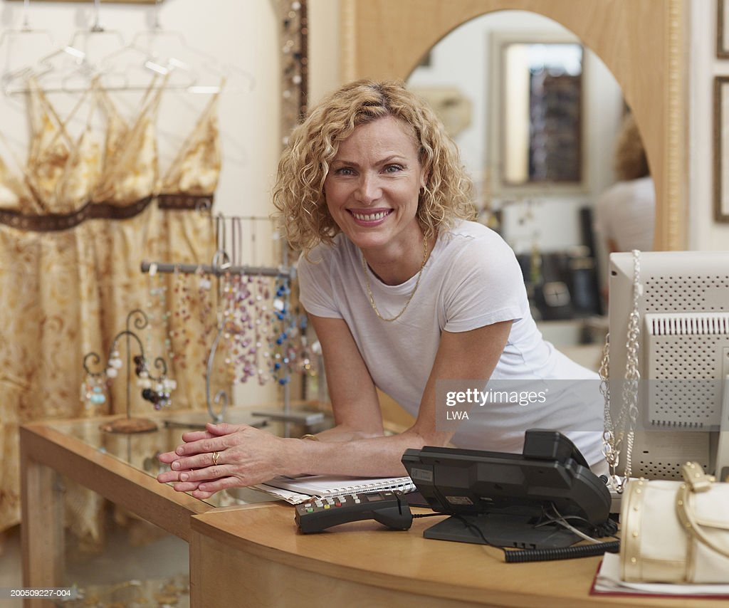 Woman behind counter in clothes shop, smiling, portrait
