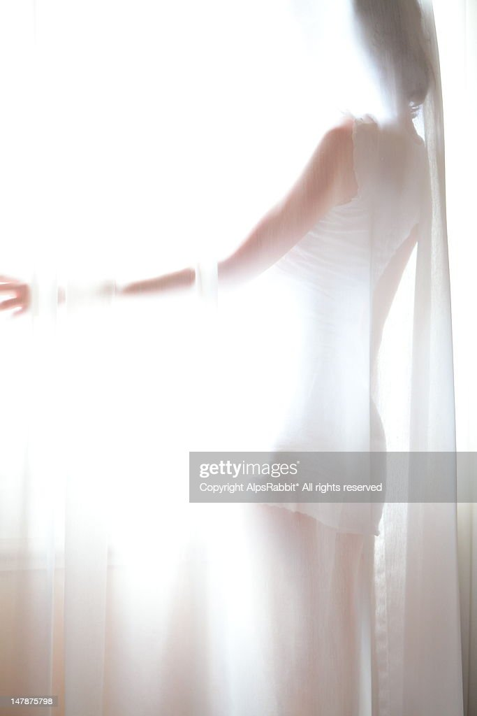 Woman behind curtains : Stock Photo