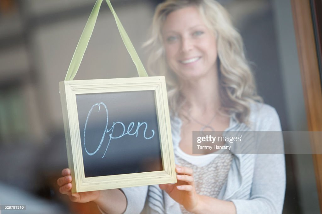 Woman behind glass door showing open sign : Stock Photo
