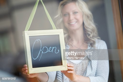 Woman behind glass door showing open sign : Foto stock