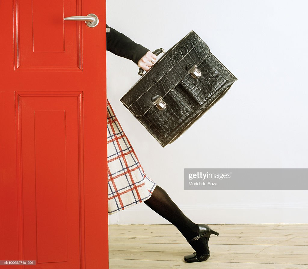 Woman behind red door carrying briefcase : Stock Photo