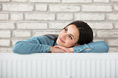 Portrait Of A Smiling Woman Behind The Heating Radiator