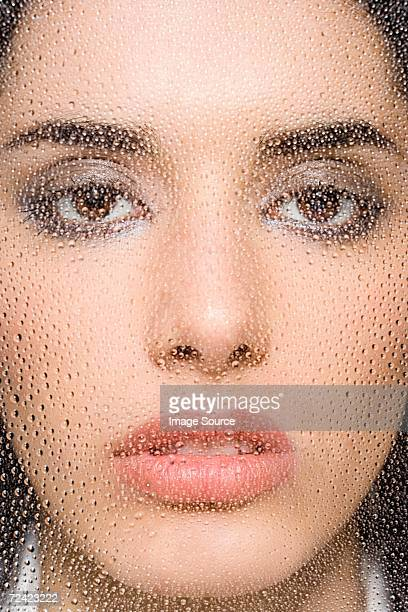 Woman behind water droplets on glass