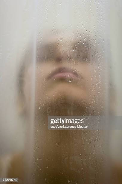 Woman behind wet shower curtain, head back, close-up