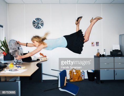 Woman being blown away by a fan. : Stock Photo