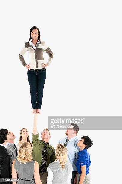 Woman being held up by her coworkers