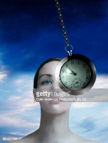 Woman being hypnotism with pocket watch : Stock Photo