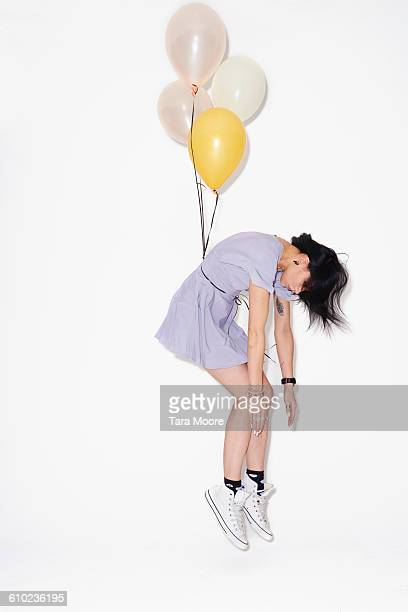 woman being lifted by balloons