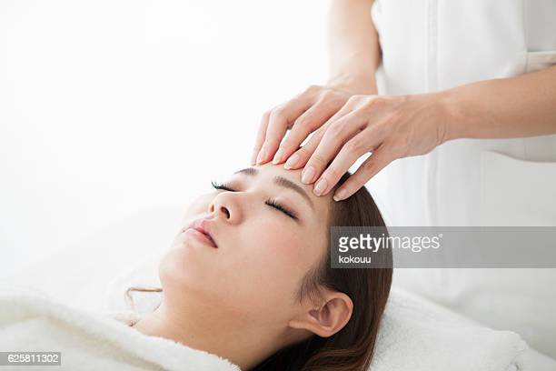 Woman being massaged by a salon with her forehead