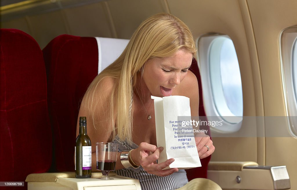 Woman being sick on plane with alcohol : Stock Photo
