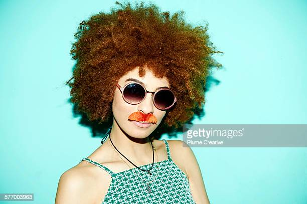 Woman being silly and wearing a stick on mustache.