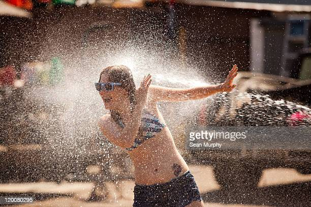 Woman being sprayed by water hose