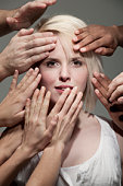 Woman being touched by many hands