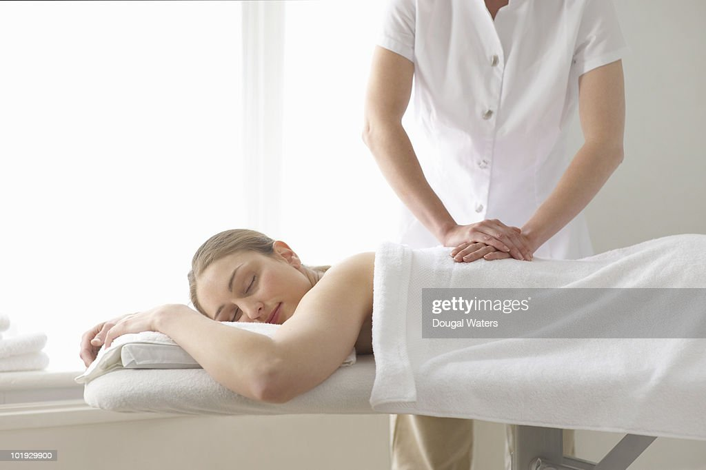 Woman being treated by masseuse. : Stock Photo