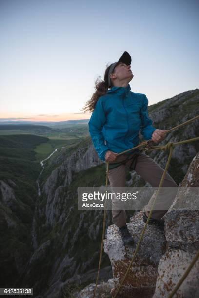 Woman belaying her climbing partner on a high cliff