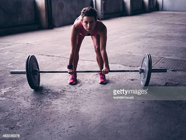 Mulher dobrar sobre a levantar Haltere com pesos pesados