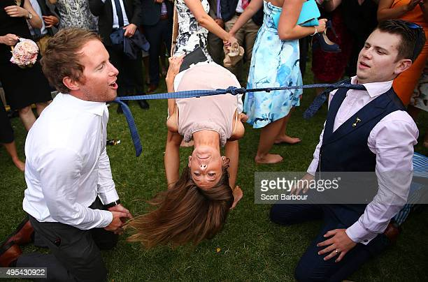 A woman bends backwards between two racegoers who have their ties tied together as racegoers play a game of Limbo following 2015 Melbourne Cup Day at...