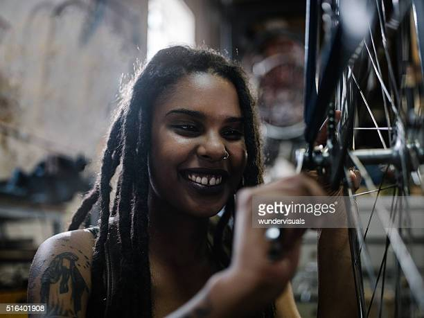Woman bicycle mechanic with dreadlocks working in bike repair wo