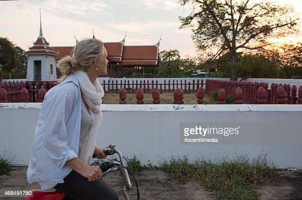 Woman bicycles past Thai temple at sunrise