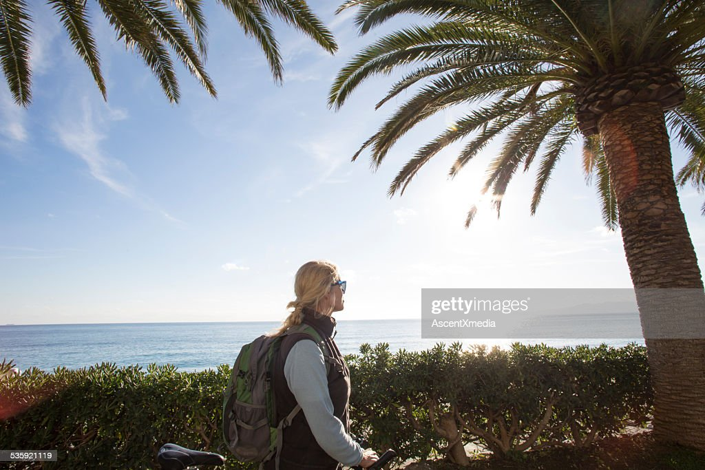 Woman bicyclist looks out from behind hedge, to sea : Stock Photo