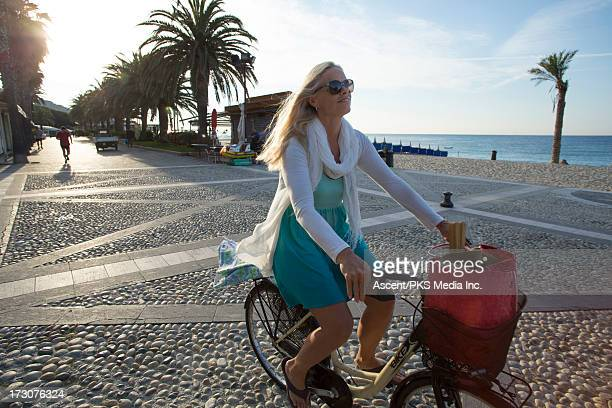 Woman bikes along beach promenade, sunrise