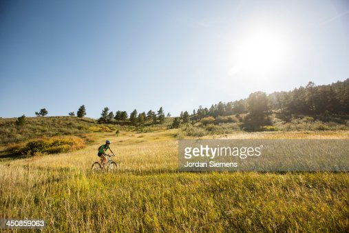 Woman biking on a dirt path.