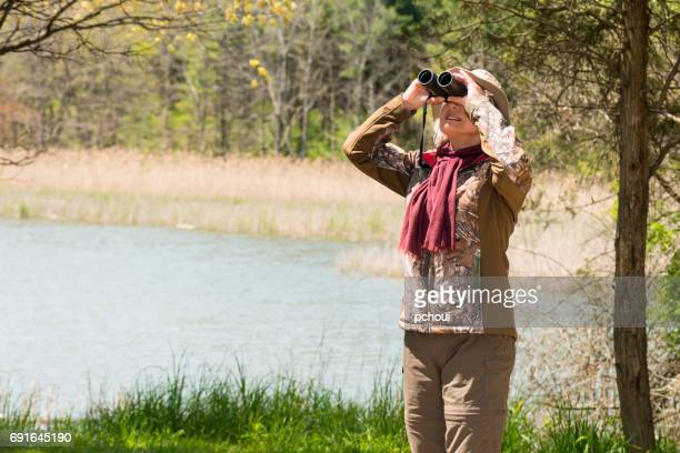 Woman birding, bird watching, active senior