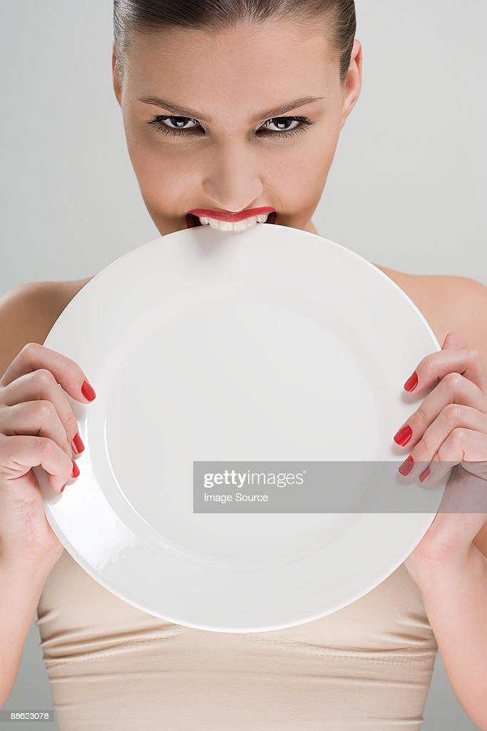 Woman biting a plate : Stock Photo