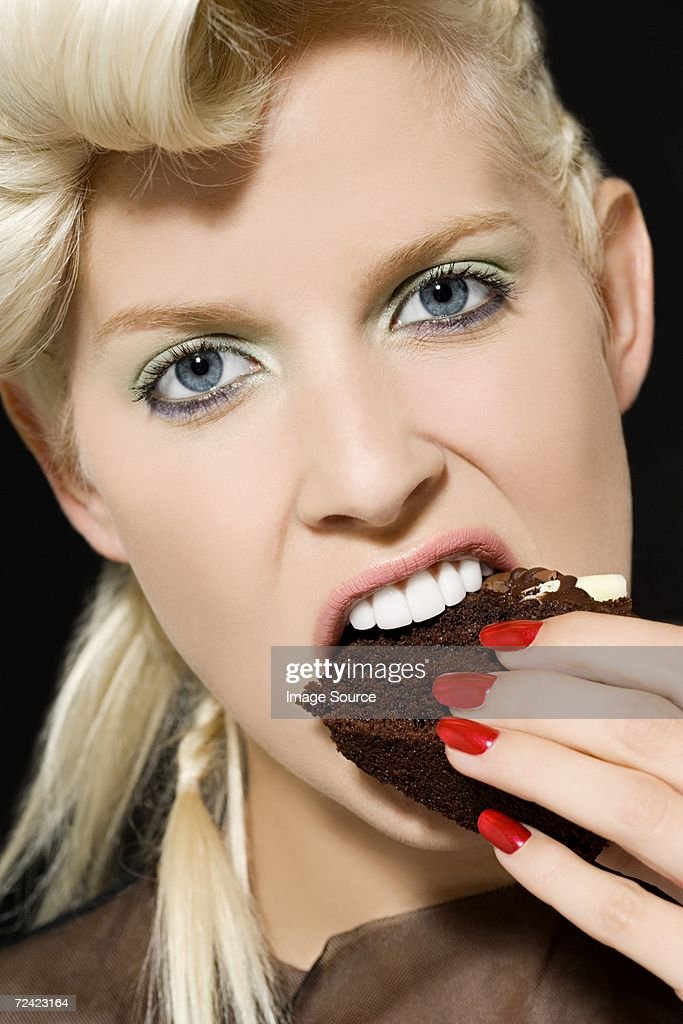Woman biting a slice of cake : Stock Photo