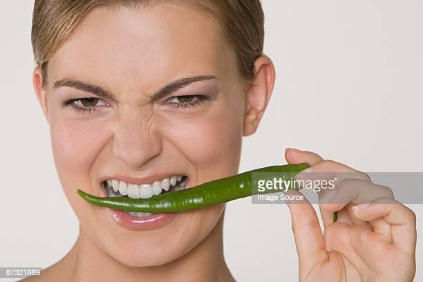 Woman biting chilli pepper