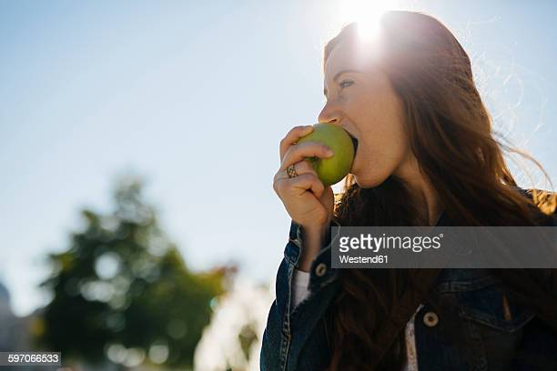 Woman biting into an apple