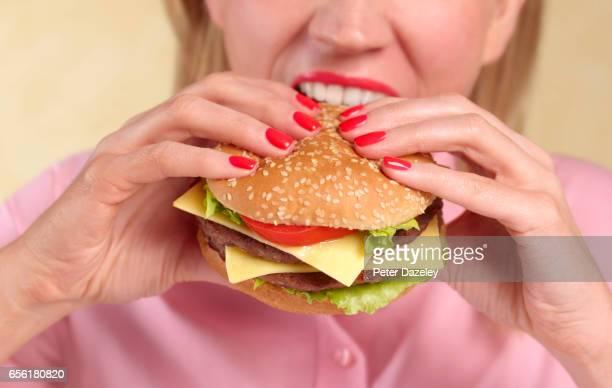 Woman biting into hamburger