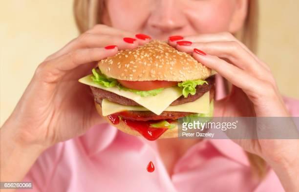 Woman biting into hamburger with ketchup drip