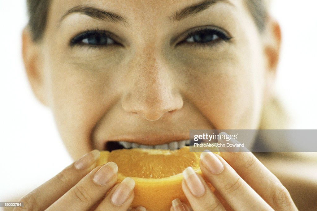 Woman biting into orange slice