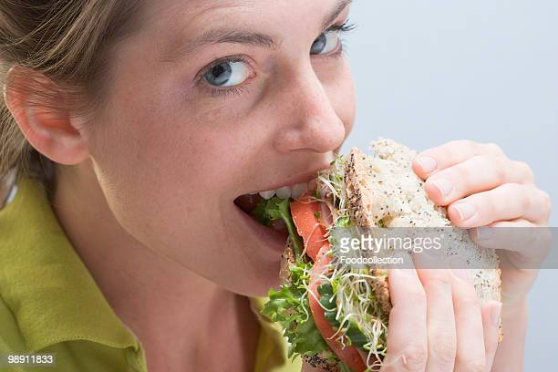 Woman biting into sandwich, close-up