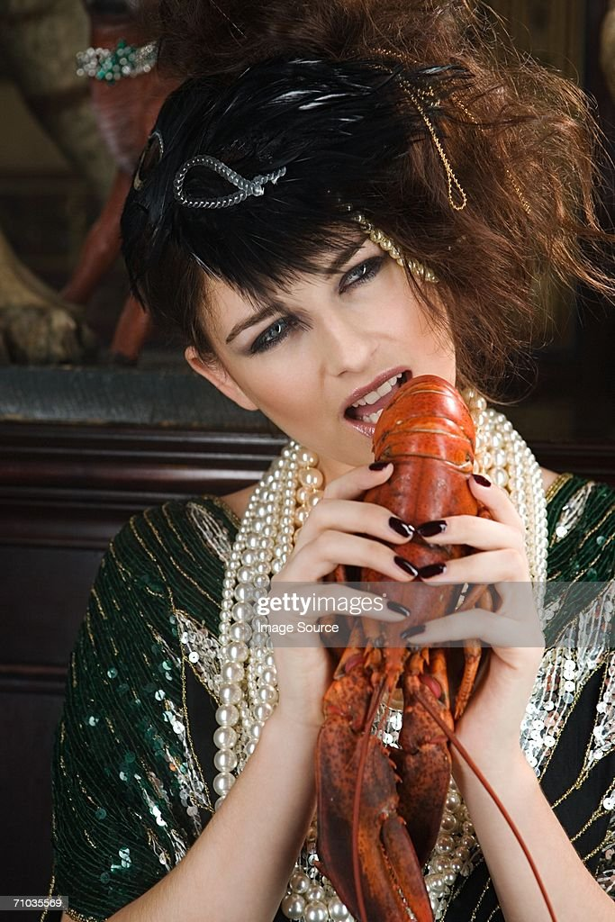 Woman biting lobster : Stock Photo
