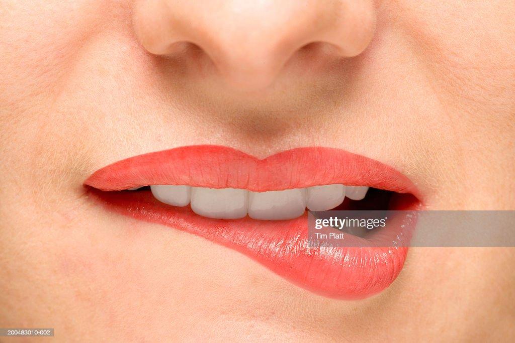 Woman biting lower lip, close-up : Stock Photo