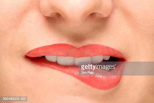 Woman biting lower lip, close-up : Stockfoto